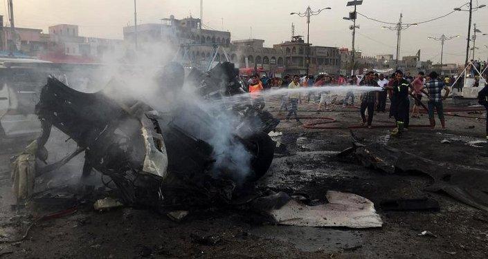 Bombeiros iraquianos apagam fogo  após explosão de carro-bomba no distrito xiita de Sadr City, em 5 de agosto de 2015
