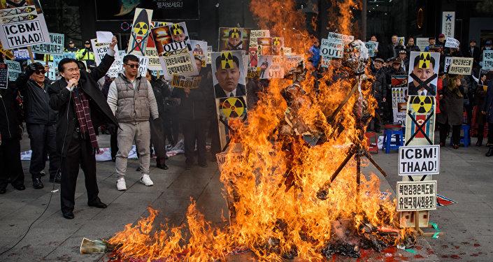 Ativistas sul-coreanos queimam cartazes com retratos do líder da Coreia do Norte, Kim Jong-un, Seul, Coreia do Sul, 11 de fevereiro de 2016