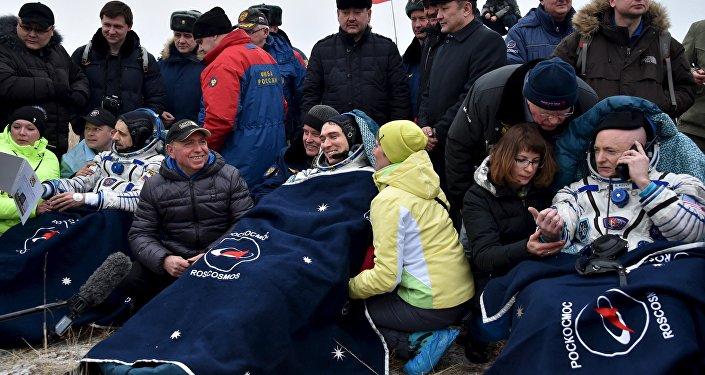 O astronauta Scott Kelly e os cosmonautas russos Sergey Volkov e Mikhail Kornienko, rodeados por pessoal logo após o desembarque, 2 de março de 2016.