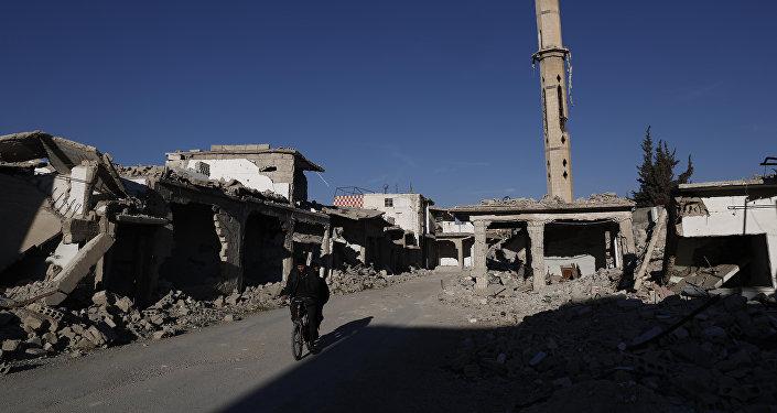 Um sírio passa em sua bicicleta pelas ruínas de Douma, cidade ocupada por rebeldes, perto de Damasco