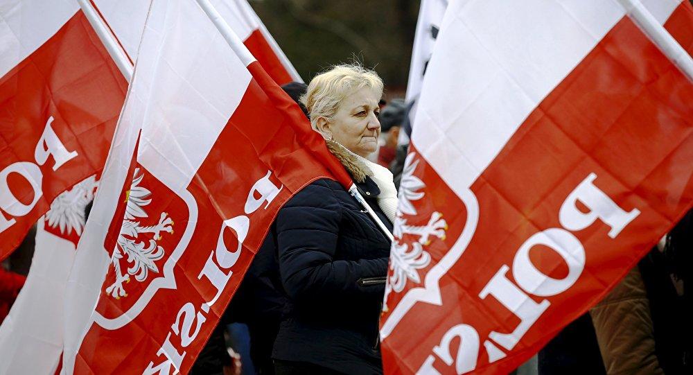 Mulher carrega bandeiras da Polônia durante protesto exigindo respeito à Constituição por parte do novo governo do país, Varsóvia, 12 de março de 2016