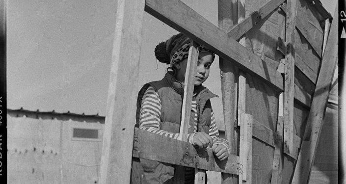 Pequena refugiada perto da casa semi-construída no Linière, Grande-Synthe, França