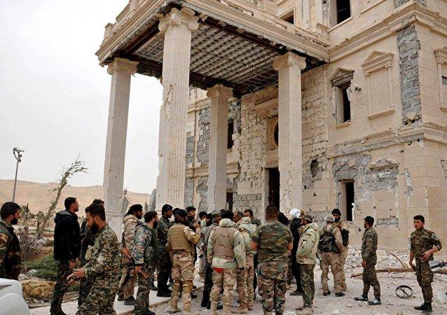 Forças leais a Bashar Assad em um complexo a oeste de Palmira