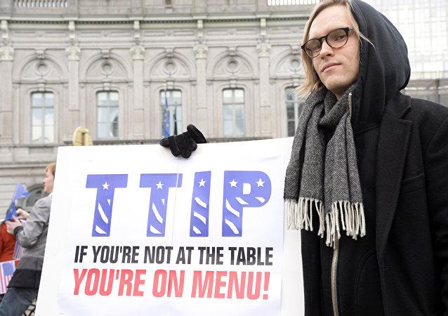 Um manifestante mostra o seu cartaz dizendo, em inglês: TTIP: se você não está à mesa, você está no cardápio durante um ato na entrada do Parlamento Europeu em 24 de fevereiro de 2016