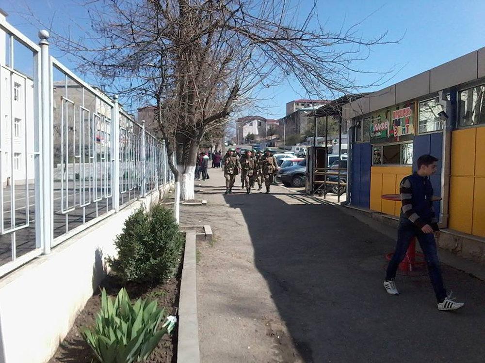 Voluntários vestindo uniforme militar vão ao local de reunião em Stepanakert