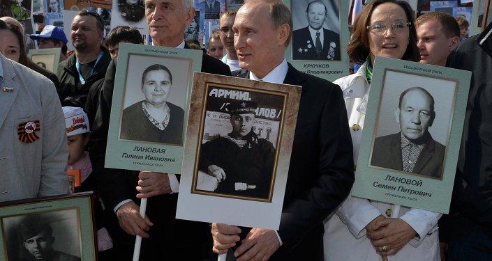 O presidente russo, Vladimir Putin com um retrato do seu pai, veterano de guerra durante a marcha Regimento Imortal na Praça Vermelha durante as celebrações do Dia da vitória em Moscovo, Rússia, 9 de maio de 2015