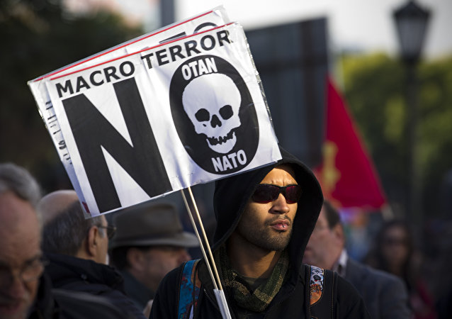 Manifestante leva cartaz com dizeres Macro terror, não à OTAN em Lisboa