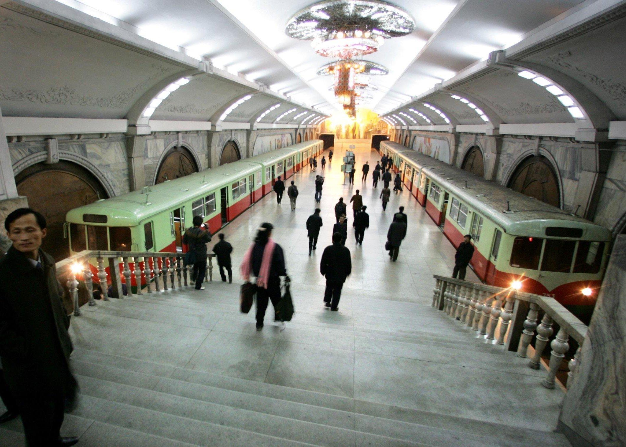 Os peões andam através a estação de metrô Puhung (ou seja, reabilitação) na capital norte-coreana de Pyongyang (Arquivo)