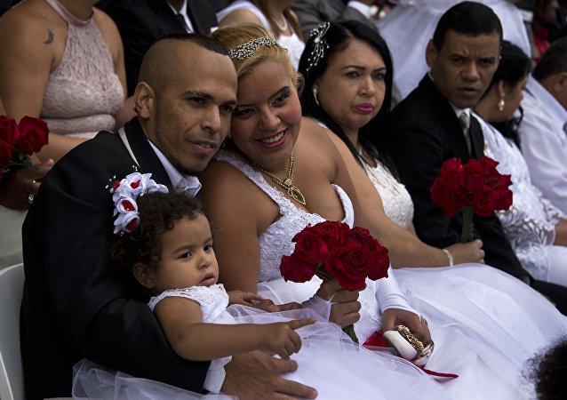 Um casal se fotografa durante uma cerimônia de casamento múltiplo em setembro de 2015 em São Paulo