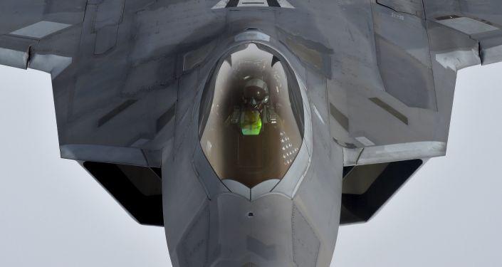 Um piloto olha para cima de uma caça americana Raptor F-22