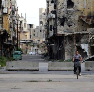 Um menino em bicicleta em uma rua na cidade síria de Homs