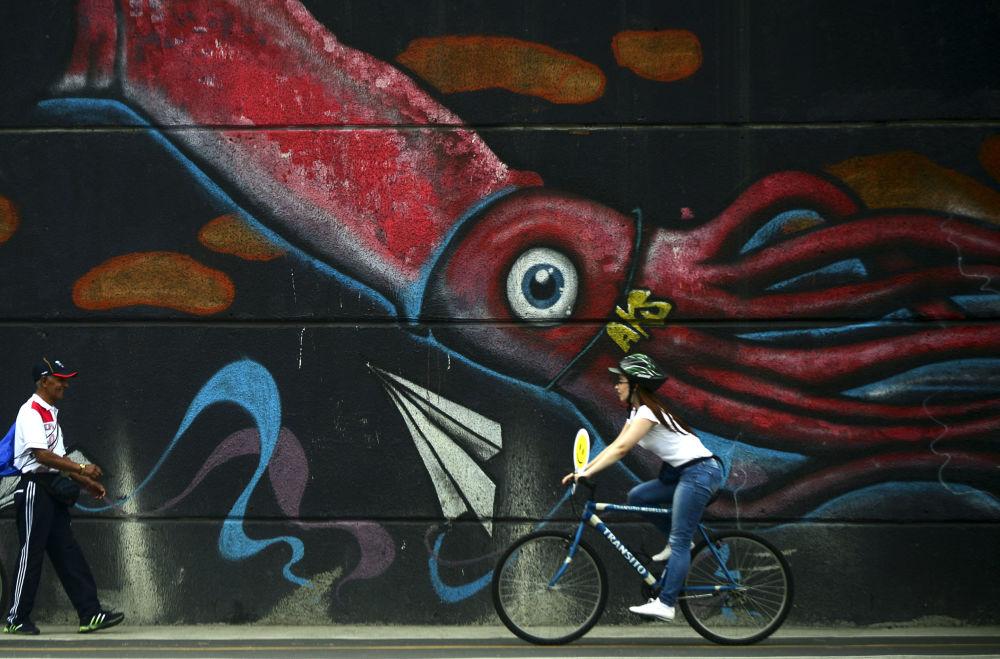 Uma colombiana vai em bicicleta diante de um grafite na cidade de Medellín.