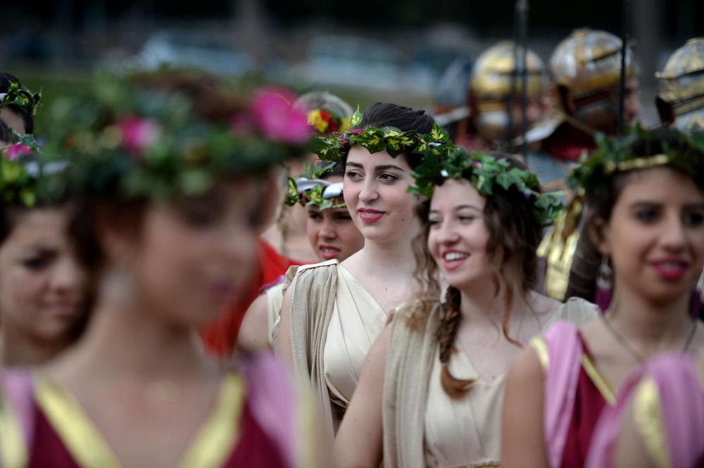 Mulheres vestem trajes de sacerdotisas da divindade Vesta antes da parada de comemoração do dia de fundação de Roma