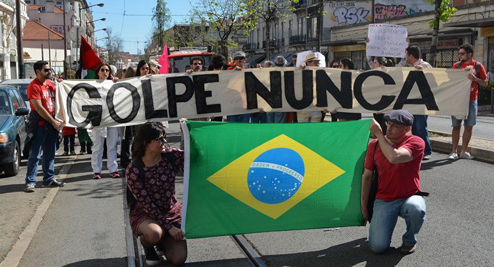 Manifestantes brasileiros mostram cartaz dizendo Golpe nunca em um ato de 1 de maio de 2016 em Lisboa