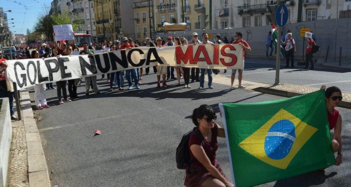 Manifestantes mostram bandeira brasileira sobre fundo de cartaz dizendo Golpe nunca mais em um ato de 1 de maio de 2016 em Lisboa