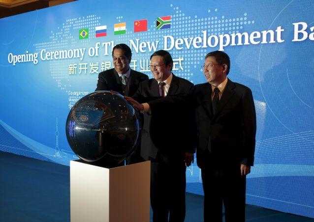 Presidente do NBD, Kundapur Vaman Kamath (esquerda), ministro das Finanças da China, Lou Jiwei (centro), e prefeito de Xangai, Yang Xiong, participam da cerimônia de abertura do Banco do BRICS