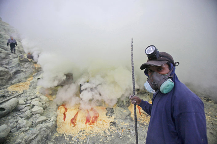 Homen na cratera do vulcão ativo de Ijen onde aldeões indonésios coletam enxofre