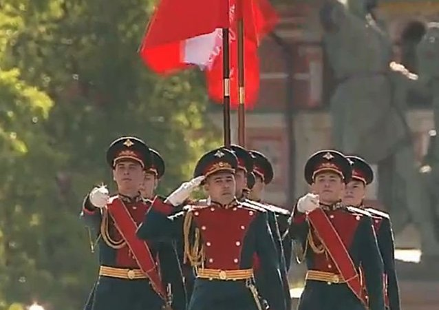 Soldados do regimento especial carregam as bandeiras da Rússia e da Vitória na praça Vermelha em 9 de maio de 2016