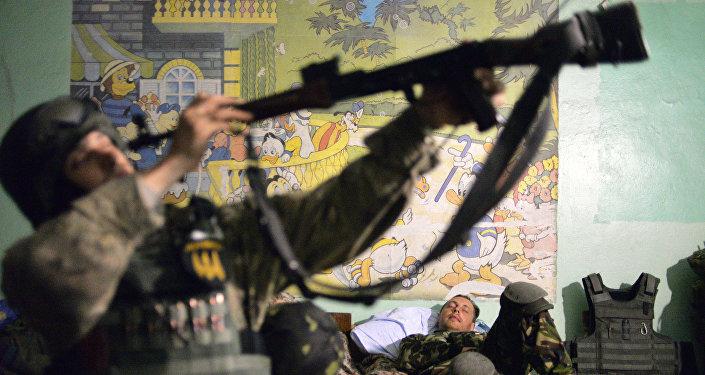 Militar ucraniano prepara sua arma para o próximo combate