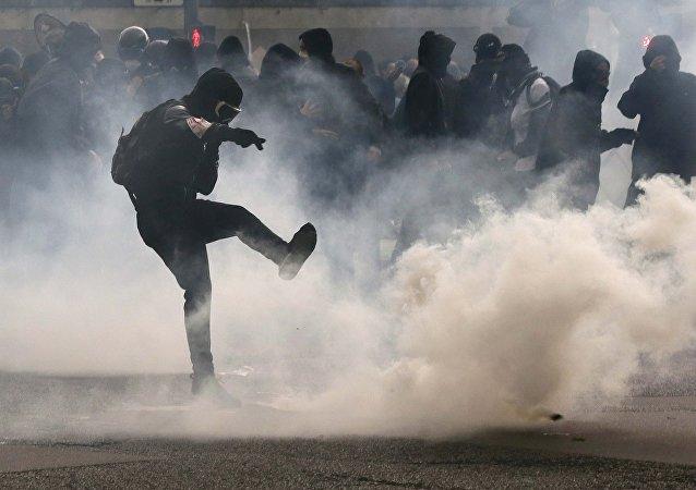 Manifestante chuta granada de gás lacrimogênio de volta para a polícia em protesto contra reforma trabalhista em Paris.