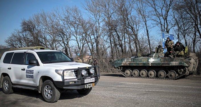 Carro da OSCE em frente a veículo militar ucraniano