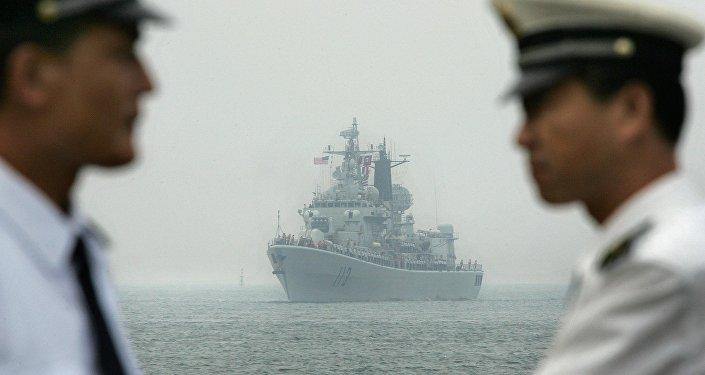 Oficiais da marinha chinesa aguardam a chegada do USS Curtis Wilbur ao porto de Quingdão