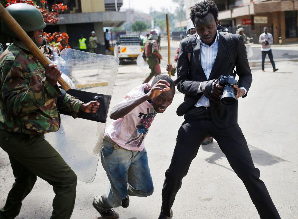 Um policial queniano bate em um manifestante durante confrontos em Nairóbi, Quênia