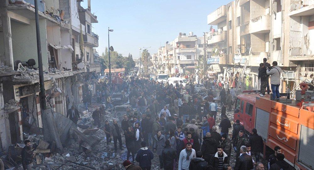 Soldados do Exército sírio, integrantes de forças de segurança e civis inspecionam local de dois bombardeios em Homs, Síria
