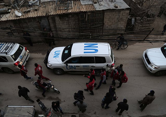 UN vehicles escorting a Red Crescent convoy carrying humanitarian aid arrive in Kafr Batna, in the rebel-held Eastern Ghouta area, on the outskirts of the capital Damascus on February 23, 2016 during an operation in cooperation with the UN to deliver aid to thousands of besieged Syrians