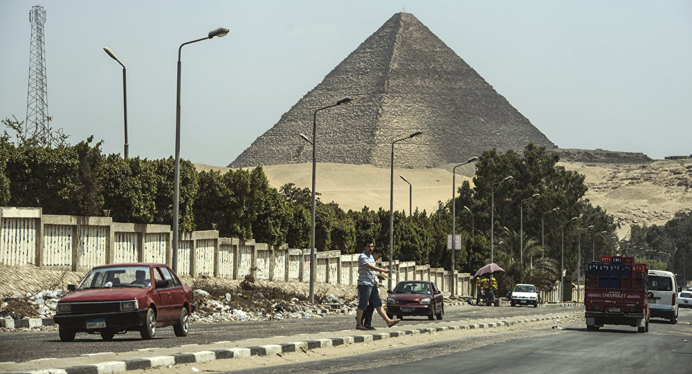 Egípcios atravessar uma estrada em frente à Grande Pirâmide de Quéops