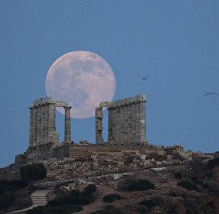 Lua aparece na frente do templo de Poséidon, no cabo Sounion, ao sudeste de Atenas, Grécia, em 20 de junho de 2016