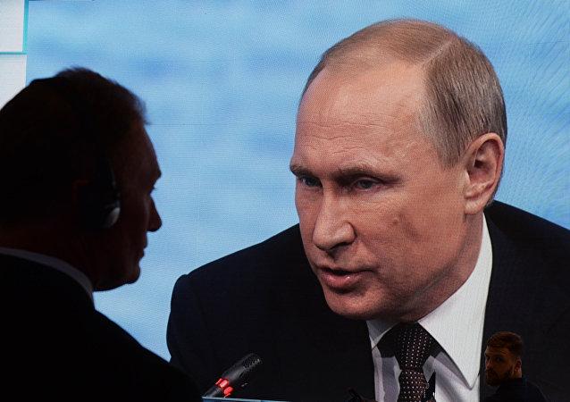 Imagem de Vladimir Putin transmitida em uma tela durante o fórum econômico SPIEF 2016