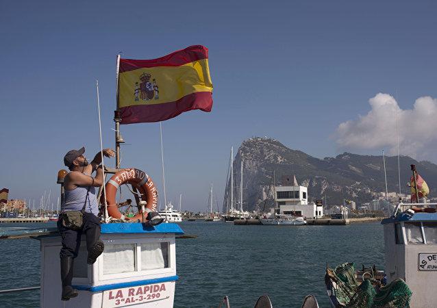 Um pescador mantém uma bandeira da Espanha no porto de La Línea de la Concepción em 18 de agosto de 2013. O porto foi palco de um protesto espanhol contra a construção de um arrecife artificial pelo governo britânico perto da península de Gibraltar, reivindicado pelo Reino Unido