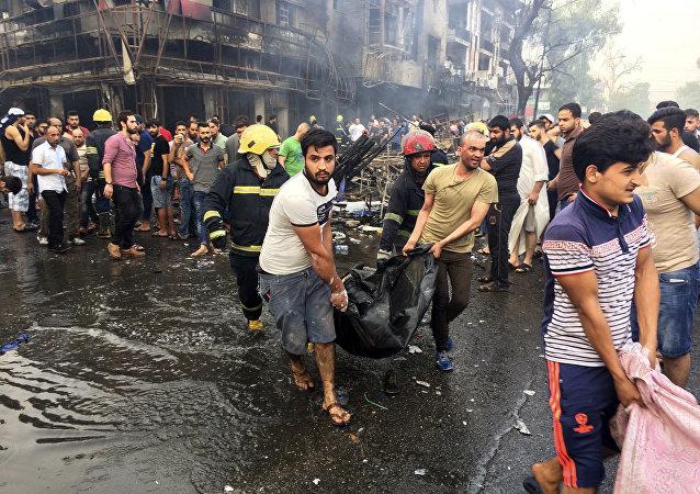 Bombeiros e civis iraquianos transportam corpos das vítimas mortos na explosão do carro-bomba na área comercial no bairro de Karada, Bagdá, no Iraque, domingo, 3 de julho, 2016