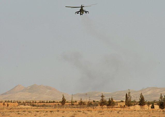 Helicóptero Mi-24 do Exército Sírio perto da cidade histórica de Palmira, na Síria