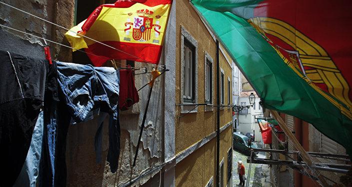 Bandeiras de Portugal e Espanha em varandas em uma rua estreita em Lisboa