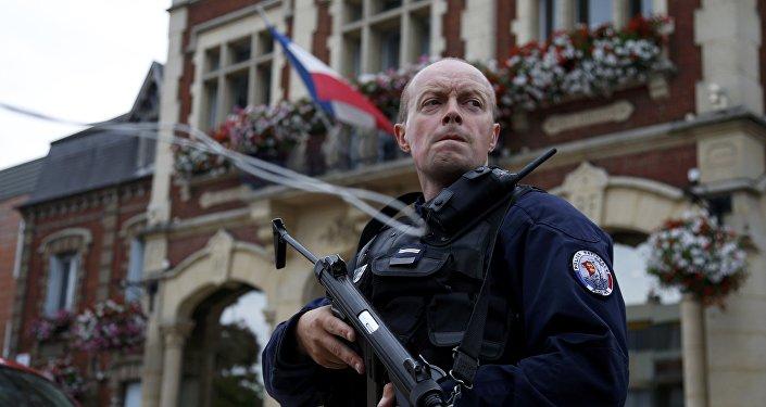 Um policial mantém vigilância em frente à prefeitura após dois assaltantes tomarem cinco reféns na igreja de Saint-Etienne-du -Rouvray, na Normandia, França, 26 de julho de 2016.