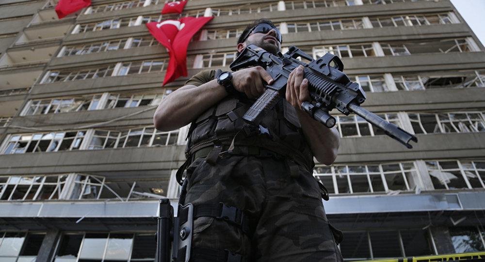 Policial das forças especiais turcas monta guarda em frente ao prédio da polícia, danificado por ataques aéreos de militares insurgidos, Ancara, Turquia