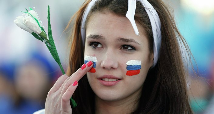 Menina com bandeiras nacionais russas pintadas na face participa de comemorações do aniversário da votação na Crimeia pela reunificação com a Rússia, em Simferopol em 16 março de 2015.