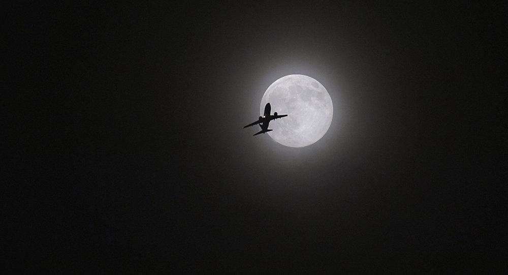 Um avião voa com a Lua em fundo sobre Kunming, no sudoeste da China, agosto de 2014