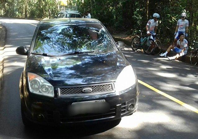 O carro com o vidro quebrado do lado do mortorista e o atleta da Coreia sentado após o acidente