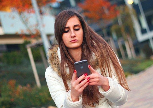 Uma menina usa seu celular