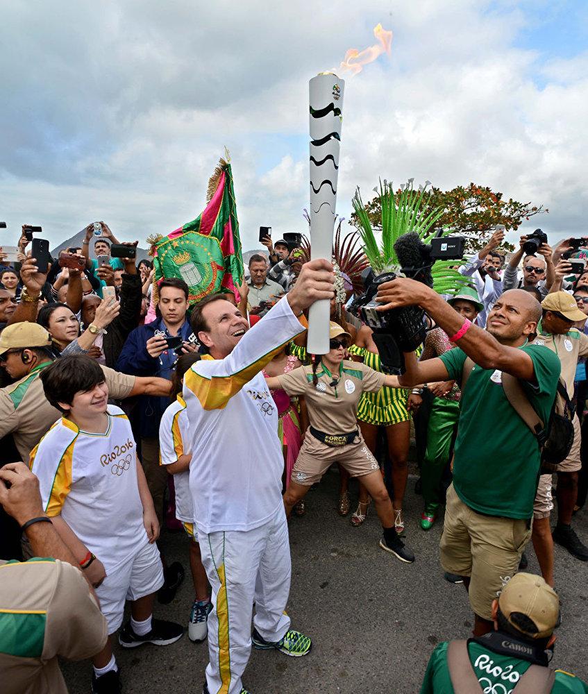 Prefeito Eduardo Paes ergue a tocha olímpica em frente à Escola Naval do Rio