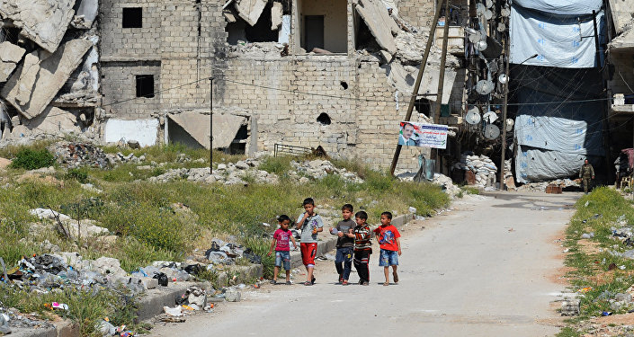 Crianças no bairro destruído da cidade de Aleppo, Síria, abril de 2016