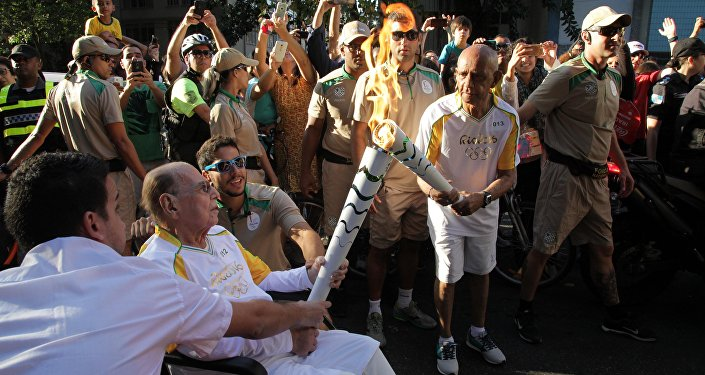 Ivo Pitanguy, de cadeira de rodas, carrega a tocha olímpica, 05.08.2016