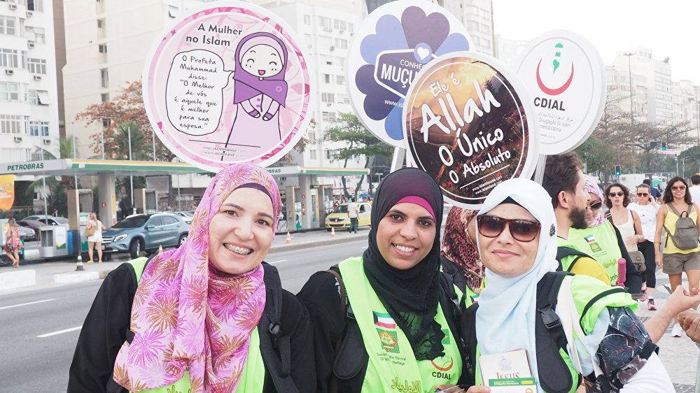 Mulheres distribuem material sobre a religião islâmica na praia de Copacabana durante os Jogos Olímpicos no Rio