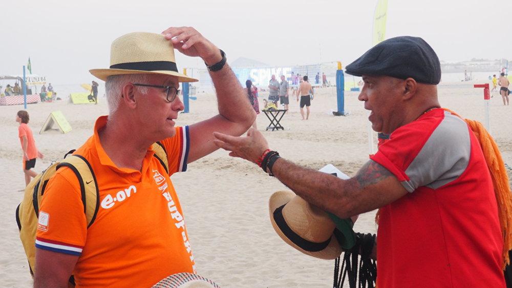 Turista holandês prova chapéu típico da malandragem carioca vendido nas praias do Rio
