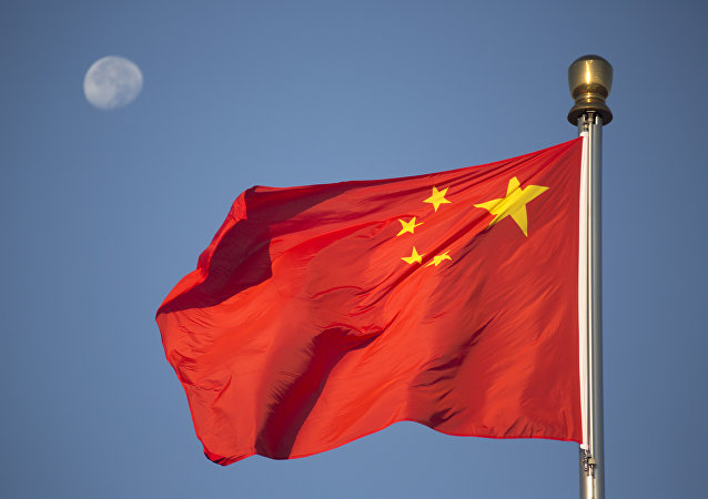 he moon sets above a Chinese flag flying over Tiananmen Square after a flag raising ceremony on National Day, the 66th anniversary of the founding of the People's Republic of China, in Beijing, Thursday, Oct. 1, 2015