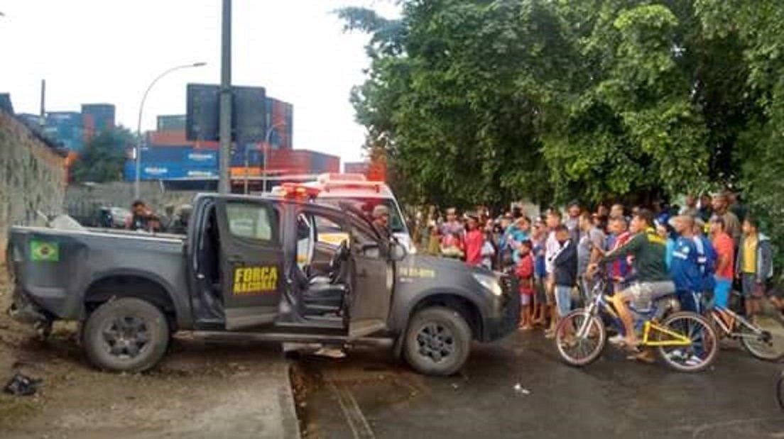 Moradores observam retirada de militares do veículo após tiroteio na Maré