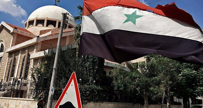 Bandeira nacional síria perto de uma igreja ortodoxa no bairro cristão da cidade de Aleppo, Síria, 12 de agosto de 2016